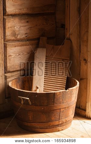 Old household equipment and machines. Wooden washboard and big bowl made of boards