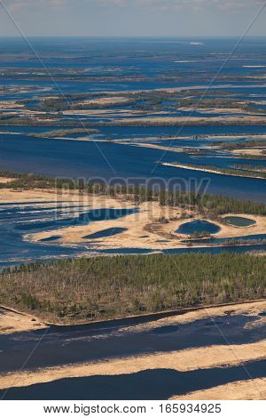 Aerial view over flood-land beside great river during spring. Great plain is divided into many parts by a lot of number of rivers and channels. Water meadows are covered by yellow last year's grass.