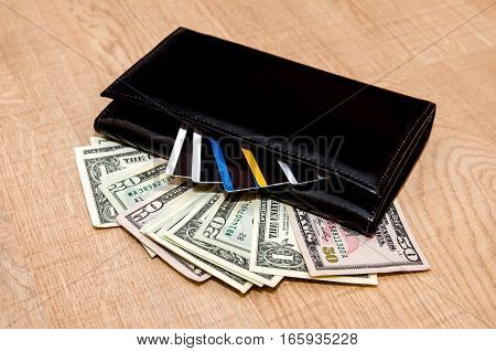 wallet with money credit cards and notepad on wood background