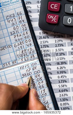 Close-up of a Businessman Writing on Bank Book with Calculator and Financial Figures