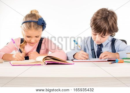 Classmates writing homework in notebooks isolated on white