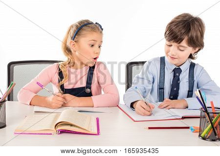 Shocked schoolgirl looking at classmate's notebook isolated on white