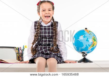 Happy schoolgirl sitting on table with globe isolated on white