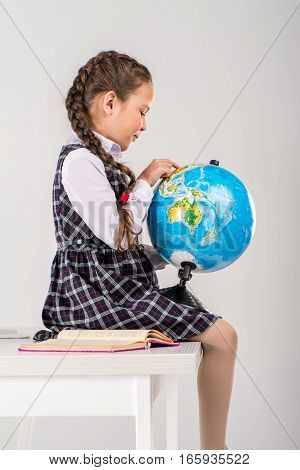 Schoolgirl exploring world on globe on grey