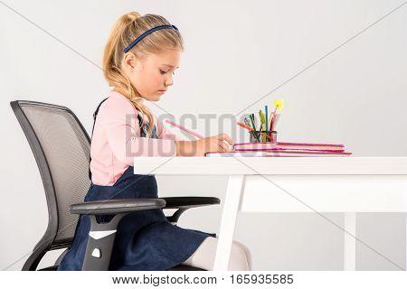 Serious schoolgirl sitting at desk and doing homework