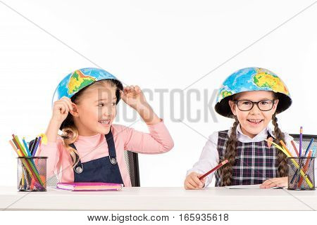 Happy schoolgirls sitting with halves of globe on heads isolated on white