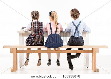 Back view of schoolchildren studying at desk on white