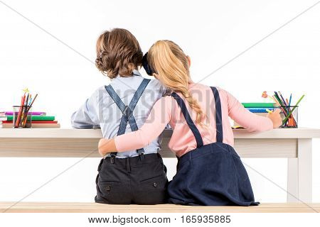 Back view of classmates sitting at desk and hugging while doing homework