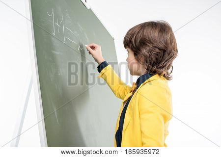 Schoolboy writing with chalk on green blackboard