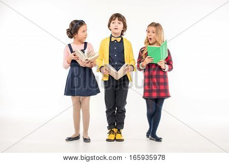 Schoolchildren standing with books on white background