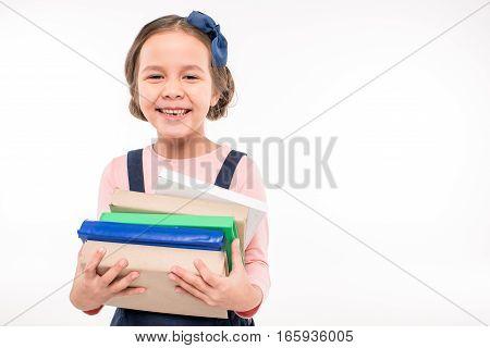 Smiling schoolgirl holding books on white background