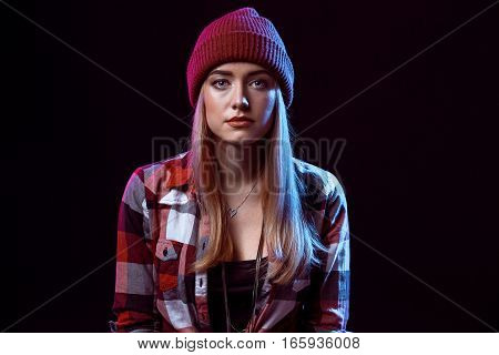 Charming casual girl, wearing in red and black plaid shirt and hat on a black background. Young woman looking into the camera