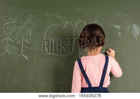 Back view of schoolgirl drawing on blackboard