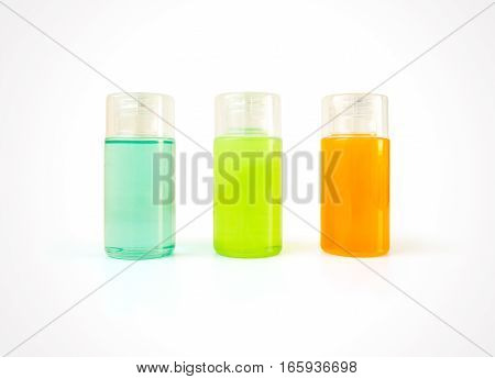Three small plastic bottles full of colorful cosmetic products with copy space. Body care and beauty products for bath in blank containers - shower gel shampoo conditioner
