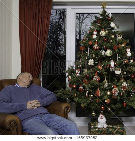 Typical English Domestic Christmas Tree decorated with lights and baubles next to man asleep in leather arm chair.