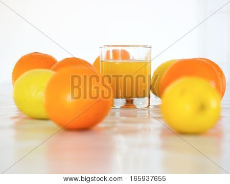 sweet and rip oranges and lemons with white background and orange juice in glass