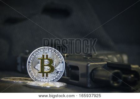 Shiny Bitcoin coin with gun and black mask