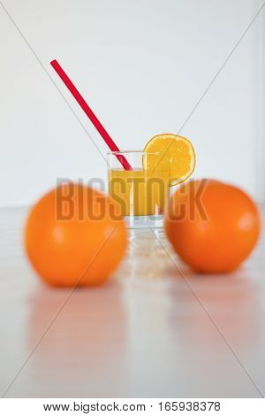 fresh orange juice in glass with the slice of orange two oranges and red straw