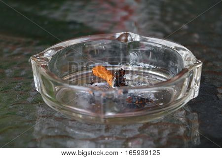 Cigarette ash in Ashtray Placed on table glass