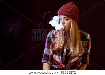 young woman smoking electronic cigarette on black background. Copy space