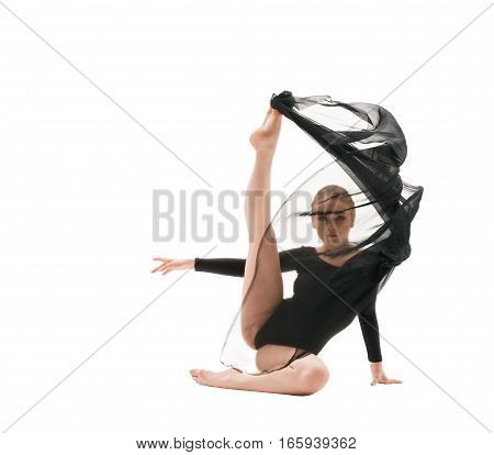 Young blonde girl in black sportsuit and transparent black cloth sitting gracefully on the floor with her leg stretched upward studio shot