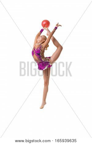 Young blonde girl in artistic embroidered violet sportsuit exercising with a red ball studio shot