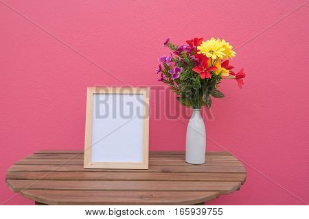 photo Frame on a wooden and Flowers in jar on pink background .