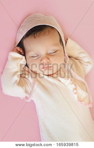 Beautiful newborn baby girl with pink hat and blue eyes closeup