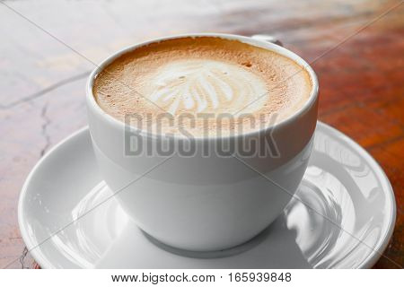 close up coffee cappuccino on the wooden floor background