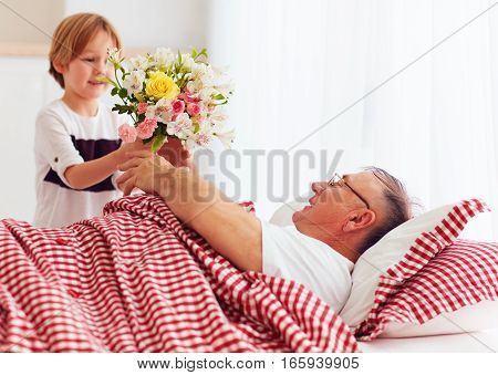 Young Grandson With Flower Bouquet Came To Visit His Sick Grandpa In Hospital Ward