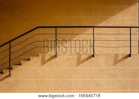 Abstract architecture. A beige wall with a ladder and a handrail. Architectural details.