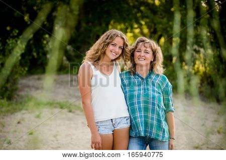 Daughter posing with her mother against nature background