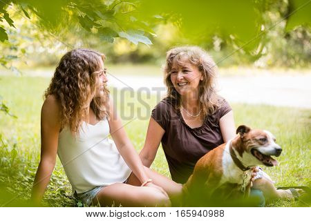 Mature woman with teenage daughter and pet dog in park.
