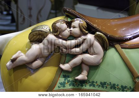 two wooden cupid  carvings with wings kissing