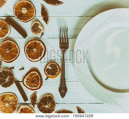 White empty plate with a fork on a white vintage wooden surface serving with dry slices of citrus fruits top view vintage toning