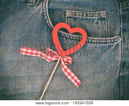 Red wooden heart on a background of blue worn jeans closeup