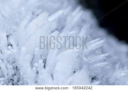 Closeup image of small ice crystal sheets, over a black background.