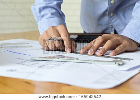 Close up architect pointing on blueprint architectural concept