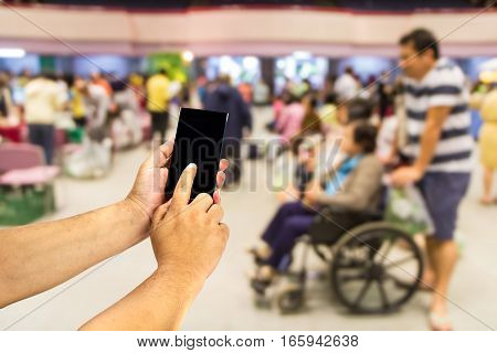Mobile phone in hand on out-patient department blurred background