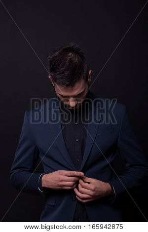 Young Man Model Looking Down Buttoning Jacket Suit