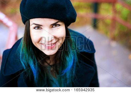 A smiling girl in a black beret with blue hair. Turquoise hair girl in a beret.