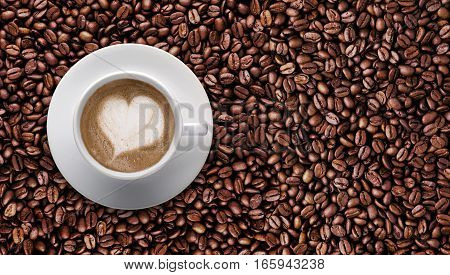 Top view - Coffee cup of LATTE ART Love symbol lover sign on top Pile of brown coffee beans with copy space for text or graphic design. Cafe' latte cream on top coffee in heart shape on background of raw coffee beans