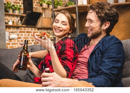 Happy couple drinking beer and eating pizza spending time together at home