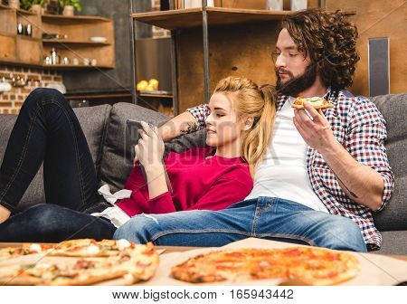 Couple spending time together at home eating pizza and using digital tablet