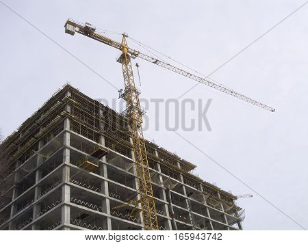Yellow construction hoisting crane above building house