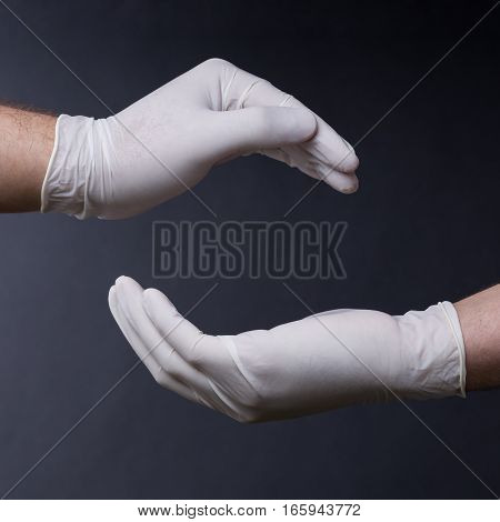 Male hands in latex gloves encircling on dark background. Place for a concept.