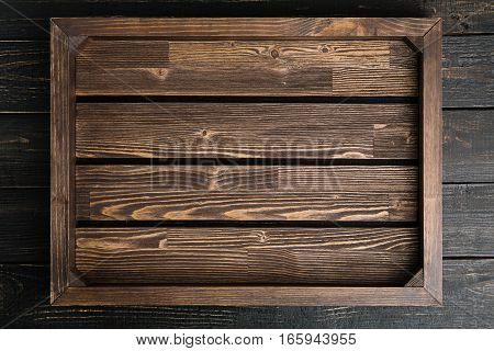 Empty brown wood serving tray on the black wooden table copy space