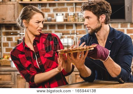 Young couple together at kitchen man showing pizza and girlfriend is disgusted