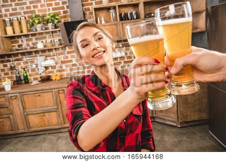 Woman toasting with beer at home party