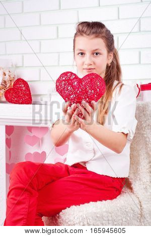 Portrait of girl sitting on chair near the valentines decorations and showing red heart